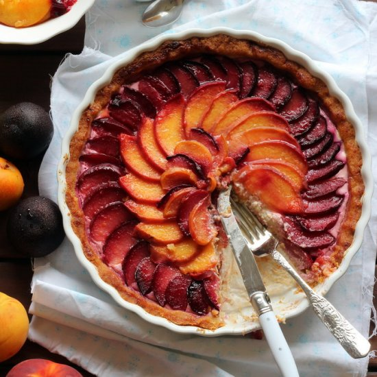 imagine this peach and plum tart with honey drizzled over it